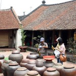 Tourists visiting an old house in Duong Lam Ancient Village