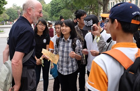 Students communicating with tourist in Hanoi