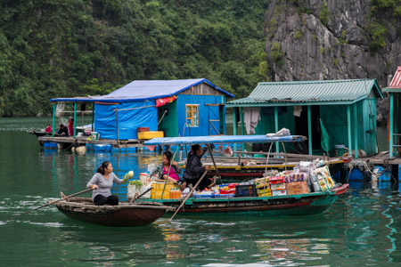 Woman buying produce from grocery boat, Vung Vieng village. Halong Bay, Vietnam
