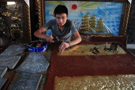 Artisan sculpturing bronze product in Dai Bai Bronze Casting Village