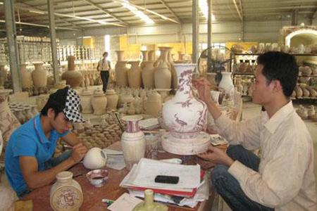 Artisans decorating ceramic product at a workshop in Chu Dau Village