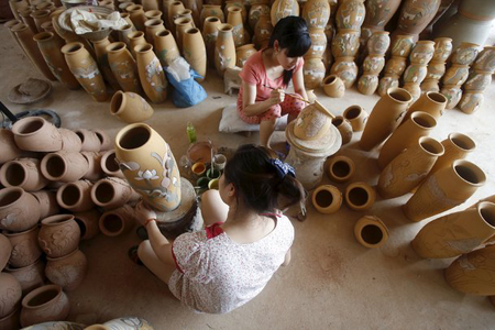 Artisans decorating pottery products in Phu Lang Pottery Village