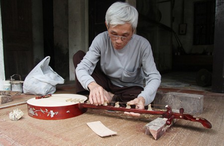 Artisan adjusting the strings of the instrument