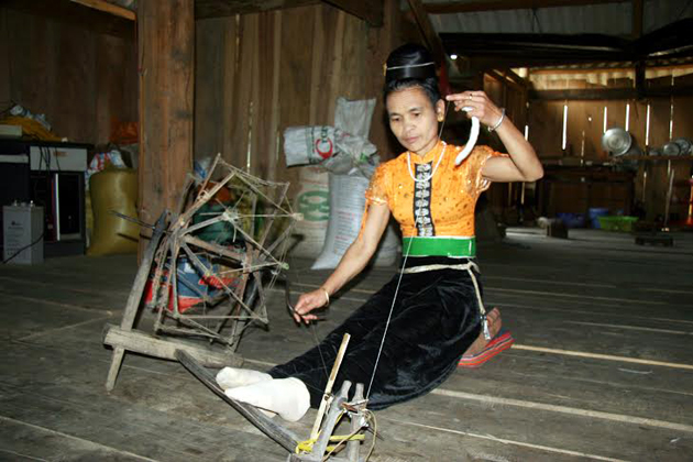 Thai woman weaving in her traditional house in the village