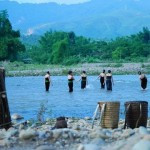 Young Thai girls in the river leave load of wood and back-baskets in the bank